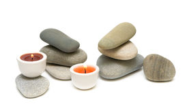Kerzen und Seekiesel auf weißem Hintergrund Stockfotografie