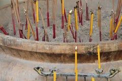Kerzen und Stock des Weihrauchs wurden zerschmettert in einer Urne (Thailand) Stockfotografie