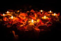 Kerzen unter den Blumenblättern von Rosen Stockbild