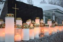 Kerzen vor einem schwarzen christlichen Grabstein Stockbild