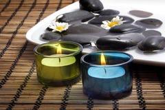 Kerzen vor schwarzen Kieseln Stockfotografie