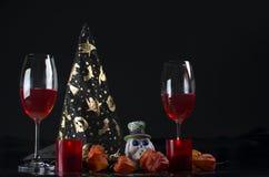 Kerzenhalter in Form von einem Schädel und zwei Gläsern Saft Lizenzfreie Stockfotos