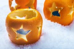 Kerzenhalter schnitzte aus Orange im Schnee heraus stockbild
