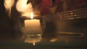 Kerzenlicht, Kerze, die im weißen Kerzenständer in der Glasminischüssel, Nahaufnahme des niedrigen Winkels falming ist stock footage