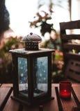 Kerzenständer auf der Terrasse und der roten Kerze stockbild