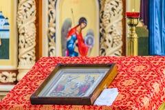 Kerzenständer mit brennender Kerze über Kanzel mit einer Ikone für Liturgie, Gebete und Predigten in der orthodoxen Kathedrale Lizenzfreies Stockfoto