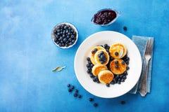 Kesopannkakor eller ostmassastruvor dekorerade honung och blåbäret i platta på blå bästa sikt för tabell Sunt och banta frukosten arkivfoto