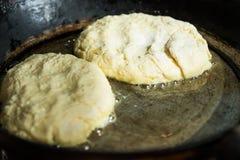 Kesopannkakor eller struvor som steker i bubblandeolja i järnensemblepannan, bykökinre Arkivfoto