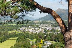 Keswick town from Castlehead viewpoint. Framed by pine branch view over town of keswick in English Lake District Royalty Free Stock Images