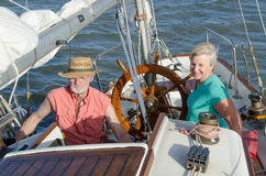 Ketch the Wind. A happy senior couple enjoys time together sailing on a lake on a fine summer day Stock Images