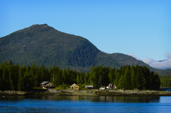 Ketchikan, Alaska. Homes at the base of a mountain nestled in evergreen trees on the water, with reflections, in the island community of Ketchikan, Alaska, a Royalty Free Stock Image