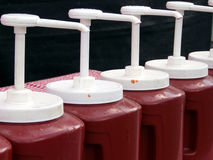 Ketchup Brigade. Line of jumbo size ketchup dispensers at a county fair Royalty Free Stock Photography