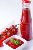Ketchup, catsup in a bottle and a bowl with cherry panicles toma. Ketchup, catsup in a glass bottle and a white bowl with cherry panicles tomatoes isolated on Royalty Free Stock Photography