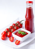 Ketchup, catsup in a bottle and a bowl with cherry panicles toma. Ketchup, catsup in a glass bottle and a white bowl with cherry panicles tomatoes  on white Stock Photos