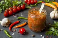 Ketchup de sauce, Lecho dans le pot en verre Ail de cerise de tomate de piment et d'autres épices sur le fond noir Photo stock