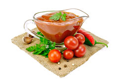 Ketchup in a glass gravy boat with vegetables on sacking Royalty Free Stock Photography