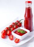 Ketchup, ketchup i en flaska och en bunke med körsbärsröd paniclestoma Arkivfoton