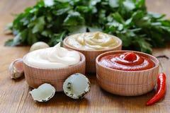 Ketchup, majonnäs och senap - tre sorter av sås Arkivbild
