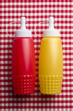 Ketchup and mustard. Bottles on gingham background Stock Photos