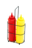 Ketchup and mustard bottles. Pair of restaurant style mustard and ketchup bottles in the rack isolated on the white background royalty free stock photos