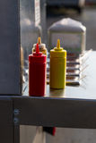 Ketchup and Mustard on Hot Dog Cart. With condiments in background royalty free stock photography