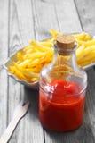 Ketchup no frasco de vidro com batatas fritas friáveis Fotos de Stock Royalty Free