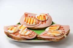 Ketchup sandwich with salami and boiled eggs on a green plate an Stock Images