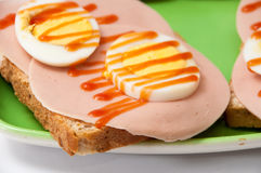 Ketchup sandwich with salami and boiled eggs on a green plate an Royalty Free Stock Photos