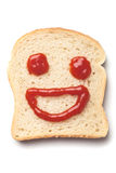 Ketchup smiley. Laughing smiley made from ketchup and slice of bread, isolated on white background Royalty Free Stock Image