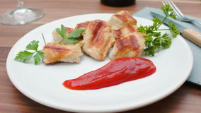 Ketchup is spread with a spoon on plate with turkey. Ketchup is spread with a spoon on white plate with grilled turkey stock footage
