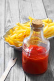 Ketchup sur le pot en verre avec les pommes frites croustillantes Photos libres de droits