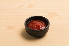 Ketchup in zwarte kom Royalty-vrije Stock Foto's