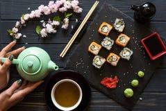 Ketel in handen van het meisje op het bureau dichtbij de sushi royalty-vrije stock afbeeldingen