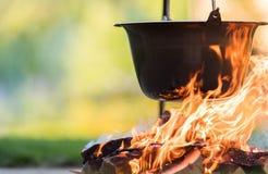 Ketel op de brand, die in de aard koken stock fotografie