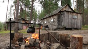 Ketel over kampvuur dichtbij hut in bos stock footage