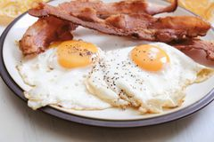 Keto bacon and eggs. Ketogenic breakfast of bacon and eggs, salt and pepper royalty free stock images