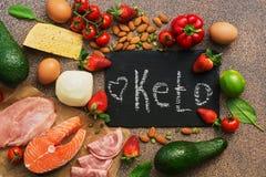 Keto bantar mat Sunda låga carbsprodukter Keto bantar begrepp Grönsaker fisk, kött, muttrar, frö, jordgubbar, ost på en brunt fotografering för bildbyråer