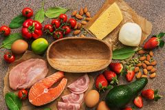 Keto diet concept.Healthy foods low in carbohydrates. Salmon, chicken, vegetables, strawberries, nuts, eggs and tomatoes, empty. Wooden bowl. Top view royalty free stock images