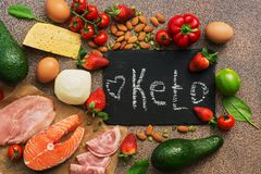 Keto diet food. Healthy low carbs products.Keto diet concept. Vegetables, fish, meat, nuts, seeds, strawberries, cheese on a brown. Background Top view stock image