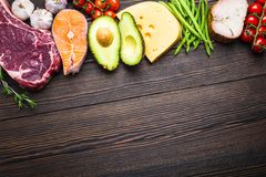 Keto diet foods. Ketogenic low carbs ingredients for healthy weight loss diet, top view, copy space. Keto foods on wooden background: meat, fish, avocado, cheese royalty free stock photo