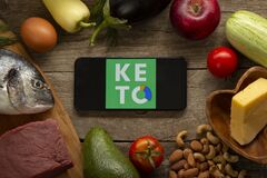 Keto Diet Recipes logo app on smartphone. Diet Plan On Tablet Pc And Vegetables. Belgorod , Russia - AUG, 18, 2020