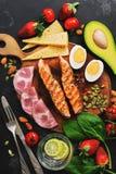 Keto, ketogenic dieet, lage koolhydraatinhoud Geroosterd zalm, groenten, aardbeien, kaas, ham en water met citroen zwart stock fotografie