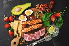 Keto, ketogenic diet, low carbohydrate content. Grilled salmon, vegetables, strawberries, cheese, ham and water with lemon. Black stock image