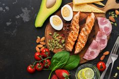 Keto lunch or dinner - grilled salmon, vegetables, boiled egg, water with lime, nuts, ham and cheese on a dark background. Ketogenic diet concept. Top view stock photography
