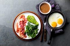 Ketogenic яичница завтрака диеты, бекон и авокадо, шпинат и противопульный кофе Завтрак низкого карбюратора высоко- тучный стоковое фото