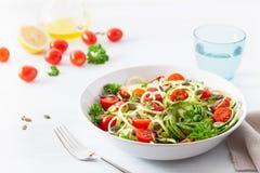 Ketogenic de veganist spiralized courgettesalade met de pompoenzaden van de avocadotomaat stock afbeeldingen