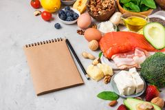 Ketogenic diet food. Healthy low carbs products. Keto diet concept. Vegetables, fish, meat, nuts, seeds, berries, cheese. With paper notebook on concrete stock image
