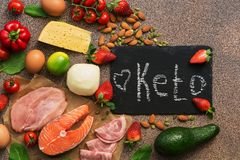 Ketogenic diet food. Healthy low carbs products.Keto diet concept. Vegetables, fish, meat, nuts, seeds, strawberries, cheese on a. Brown background. View from royalty free stock photography