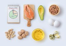 Ketogenic low carbs diet concept. Healthy eating and dieting with salmon fish, avocado, eggs and nuts. Top view. Flat lay Royalty Free Stock Image