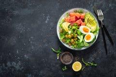 Ketogenic, paleo diet lunch bowl with salted salmon fish, lemon, avocado, olives, boiled egg, cucumber, green lettuce salad